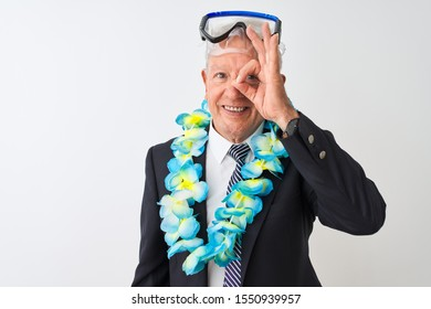 Senior businessman wearing suit hawaiian lei diving goggles over isolated white background doing ok gesture with hand smiling, eye looking through fingers with happy face.