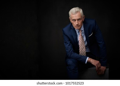 Senior businessman wearing a suit and looking thoughtfully while sitting against at dark background.