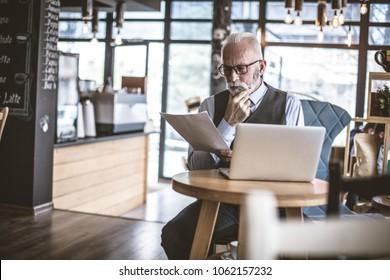 Senior businessman working at cafe.