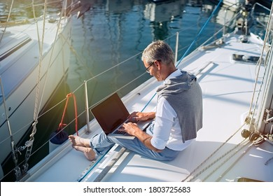Senior businessman is working during the vacation on a sailboat