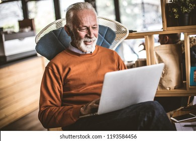 Senior businessman working on laptop at his workplace.