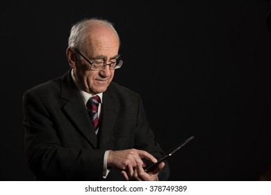 senior businessman works with tablet pc