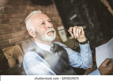 Senior businessmen thinking. Close up image.