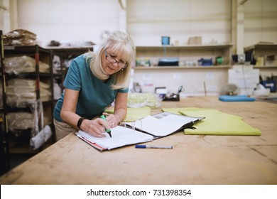 Senior businesswoman is doing paperwork in her stock factory.