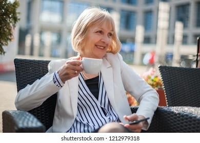 Senior businesswoman is having coffee break in cafe.