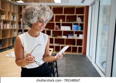 Senior businesswoman holding glasses, using smartphone