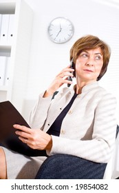 Senior businesswoman looking through window while calling on phone and working at office.