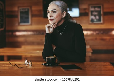 Senior businesswoman sitting at cafe table looking away and thinking. Thoughtful mature female at coffee shop.