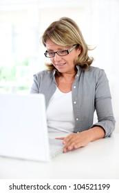 Senior businesswoman sitting in front of laptop computer