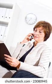 Senior businesswoman sitting at office looking at document and calling on mobile phone.