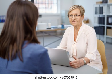 Senior businesswoman talking to a junior colleague as she sits at a table in the office with her laptop computer