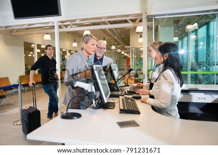 Senior Businesswoman Talking With Staff At Airport