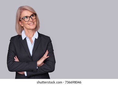 Senior businesswoman wearing glasses. Beautiful old woman looking up and thinking. isolated on grey