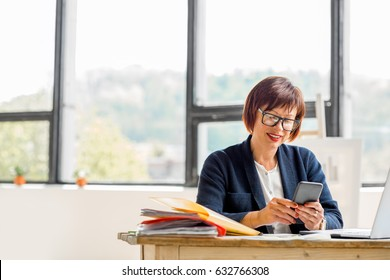 Senior businesswoman working with documents and smartphone at the bright modern office interior