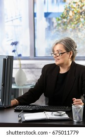 Senior businesswoman working on computer at desk in office, looking at screen, smiling.