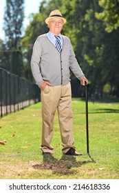 Senior with a cane posing in a park on a sunny summer day