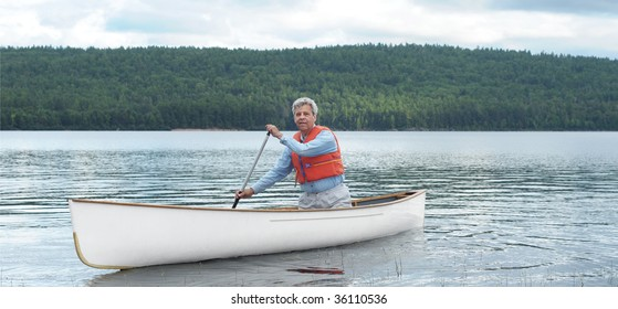 Senior canoeist paddling on quiet lake