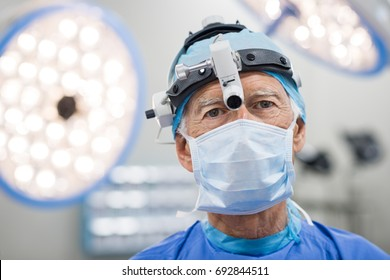 Senior cardiac surgeon with surgery equipment looking at camera. Portrait of a physician in a sterile operating room. Expertise surgeon with protective mask and cup in operating room.