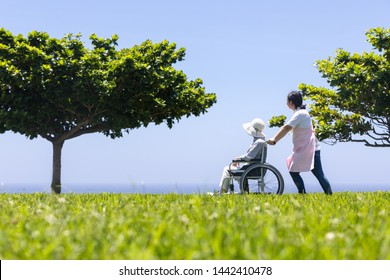 Senior and care helper taking a walk with a wheelchair