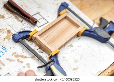 Senior carpenter glueing wooden craft surface and joining with clamps. Woodwork carpenter with equipment and tools at workshop. Handmade diy furniture.Wood part glue joiner