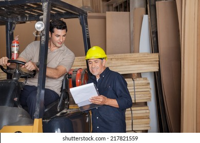 Senior carpenter holding clipboard by colleague sitting in forklift at workshop