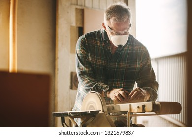 Senior carpenter sanding a wood with belt sander in carpentry workshop. Male carpenter with face mask working on belt sander machine.