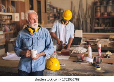 Senior carpenter is taking a coffee break from hard work. His apprentice is drilling wood in the background.