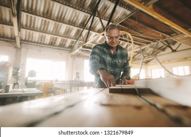 Senior carpenter works on the machine with the wooden product manufacturing. Carpenter cuts the wood of various configurations on the circular saw machine.