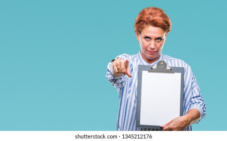 Senior caucasian business woman holding clipboard over isolated background pointing with finger to the camera and to you, hand sign, positive and confident gesture from the front