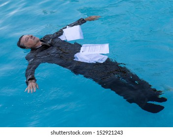 Senior caucasian businessman in suit sinking underwater in deep blue pool worried about being underwater with mortgage payments