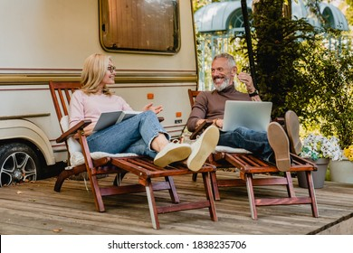 Senior caucasian cheerful couple talking in the camper van yard sitting on deck chairs with book and laptop