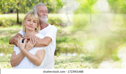 Senior Caucasian couple hugging in park. Family with a happy smile feels relaxed with nature in the morning. Or in the evening. Enter elderly society And retire from work. Concept new normal