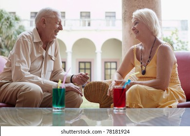 senior caucasian couple sitting in bar at hotel with cocktails and talking. Horizontal shape, side view