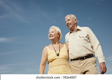 senior caucasian couple walking on sunny day and hugging. Horizontal shape, low angle view, copy space
