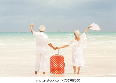 Senior Caucasian couple in white casual clothes together waving on vacation beach at tourism destination with travel luggage