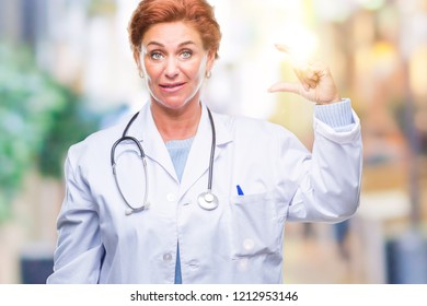 Senior caucasian doctor woman wearing medical uniform over isolated background smiling and confident gesturing with hand doing size sign with fingers while looking and the camera. Measure concept.
