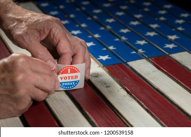 Senior caucasian hand removing sticker of I Voted Today stickers for the US elections with flag in background