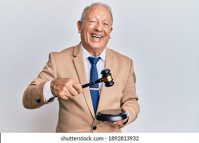 Senior caucasian judge man using gavel smiling and laughing hard out loud because funny crazy joke.