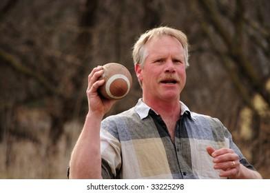 senior Caucasian male throwing football