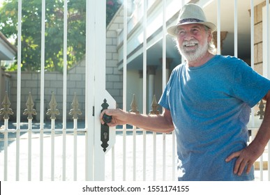 Senior caucasian man of 70 years smiling and touching the gate of his home. Tropical place in a sunny day. Summer hat