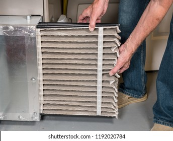 Senior caucasian man changing a folded dirty air filter in the HVAC furnace system in basement of home
