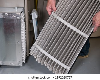 Senior caucasian man examining a folded dirty air filter in the HVAC furnace system in basement of home