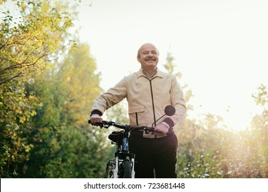 Senior caucasian man go for a walk with bike in countryside. Green trees on background. He is happy and active.