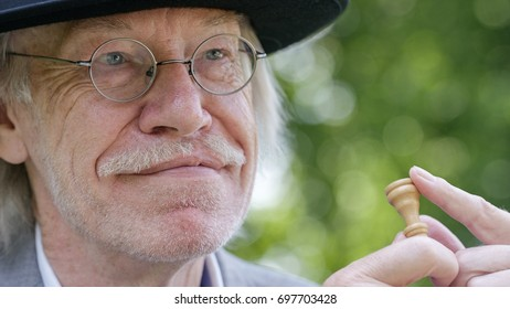 Senior caucasian man holding a chess piece while looking at his opponent