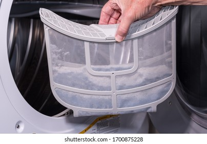 Senior caucasian man holding the lint filled trap from a front loading tumble dryer