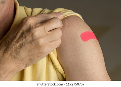 Senior caucasian man holding up shirt sleeve to show the sticking plaster after a flu jab in shoulder