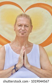 A Senior Caucasian Man Holds a Yoga Pray Pose in front of a Yellow Wall at a Silent Retreat in Oaxaca, Mexico