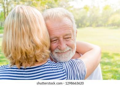 Senior Caucasian man hugging his female partner outdoor.