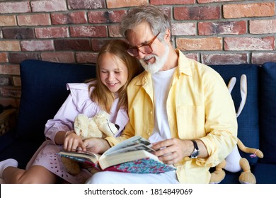 senior caucasian man and little girl looking at family photo album in living room, family concept