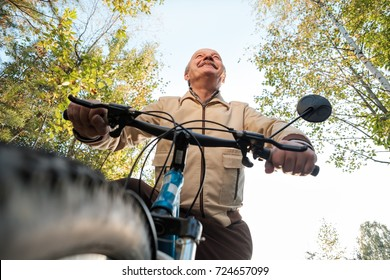 Senior caucasian man on cycle ride in countryside. Green trees on background. He is happy and active.